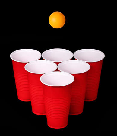 Beer pong  Red plastic cups and orange table tennis ball over black background  Closeup photo