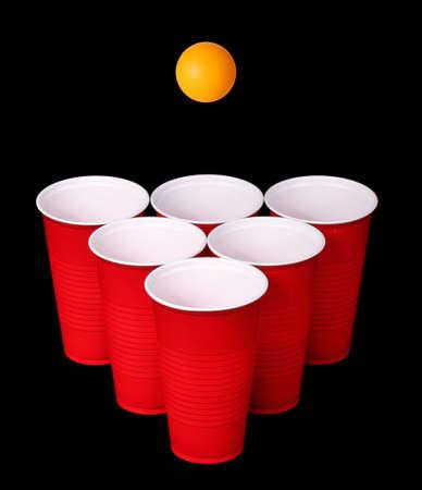 pingpong: Beer Pong vasos de plástico rojo y naranja pelota de tenis de mesa sobre fondo negro Primer plano Foto de archivo