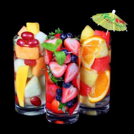 cocteles de frutas: Macedonia de frutas sobre fondo negro Rebanadas frescas de diferentes frutas en vidrio con la menta y el paraguas en la bebida sana superior