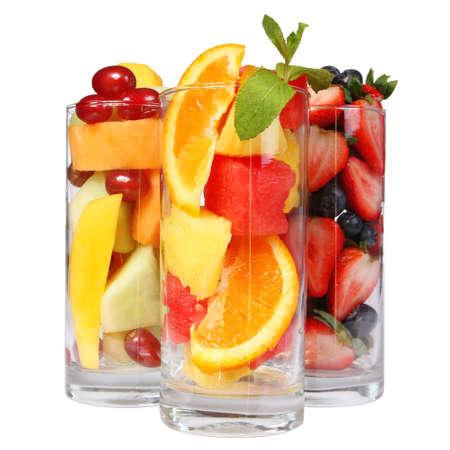 cocteles de frutas: Ensaladas de fruta aislados en rebanadas frescas blancas de diferentes frutas en copas con la menta en la bebida sana superior