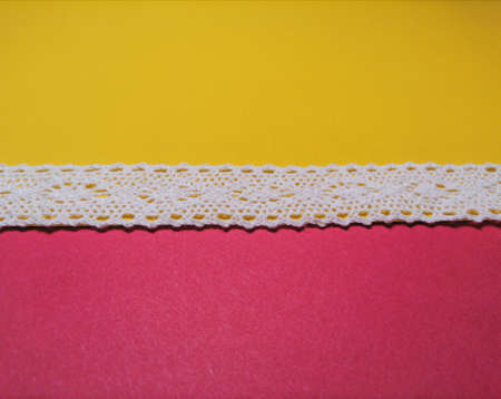 Lace on yellow and pink background Imagens