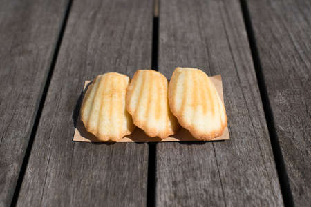 the madeleine: three madeleine cookies arranged over dark brown wooden table, exposed in daylight, horizontal