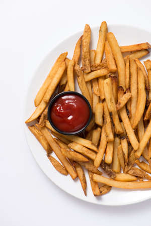 french fries plate: french fries and ketchup in a white plate as a snack, studio shot, close up, vertical