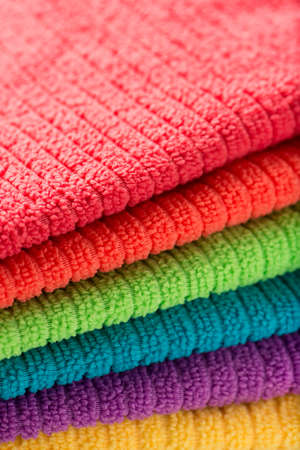 hotel bathroom: stacked or pile of bathroom towels in rainbow colors, close up, vertical Stock Photo