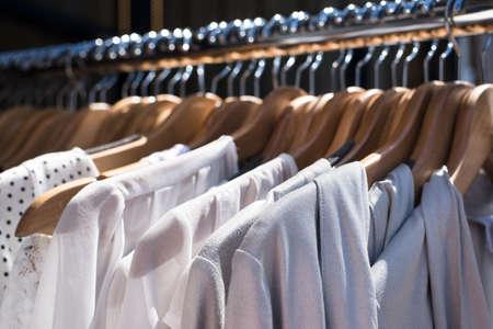 tienda de ropa: blanco y gris ropa de tono que cuelgan en un estante en una tienda de ropa de dise�o, atenci�n selectiva, horizontal Foto de archivo