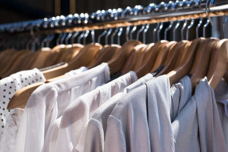 closet: white and gray tone clothes hanging on a rack in a designer clothes store, selective focus, horizontal Stock Photo
