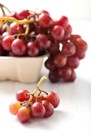 purple red grapes: bunch of ripe, organic, seedless purple grapes in recyclable box with a small cluster in selective focus, isolated over white board, close up, vertical Stock Photo
