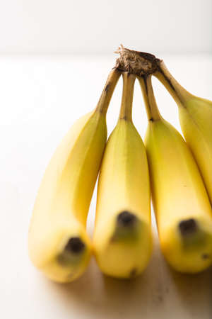 brightly: bunch of organic bananas isolated on brightly lit white background, close up, vertical