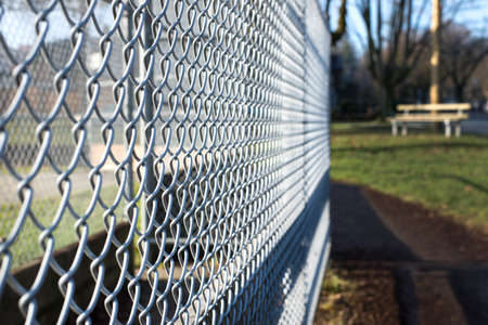 mesh fence: metal fence cage in a soccer field, park bench behind, sunny day, closeup, detail, horizontal