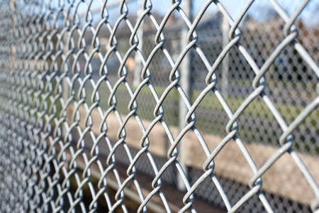 metal chain: metal fence cage in a soccer field, closeup, horizontal