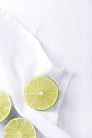 styled: freshly cut, organic lime, styled over white cutting board and kitchen cloth, top view, vertical Stock Photo