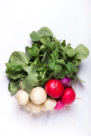 organically: bunch of organically grown, freshly harvested, colorful Easter egg radishes, isolated over white board, close up
