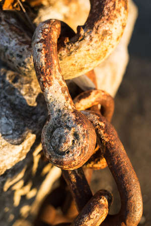 coalesce: thick rusty old chain by the beach with sunset light over chains Stock Photo