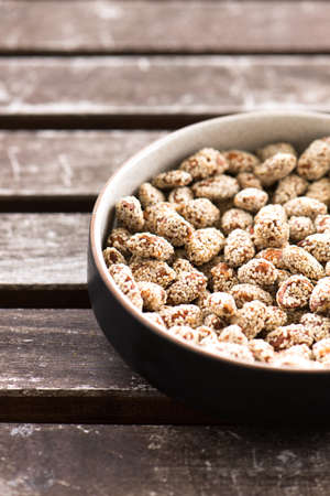 roasted sesame: almonds roasted with sesame seeds as sweet snack, in a ceramic bowl isolated on a wooden table