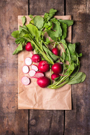 organically: bundle of organically grown, freshly harvested, red radishes with cuts on a recycled paper, isolated over rustic wooden background, close up, top view Stock Photo