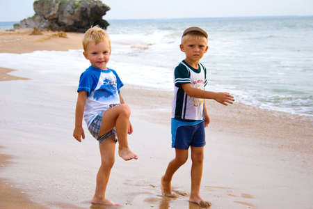 Little boys playing and walking on sea coast. Stock Photo