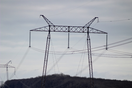 On the photo there are electrical supports, 330 kV power transmission lines, metal poles with insulators transmitting huge current over long distances Standard-Bild - 117833812