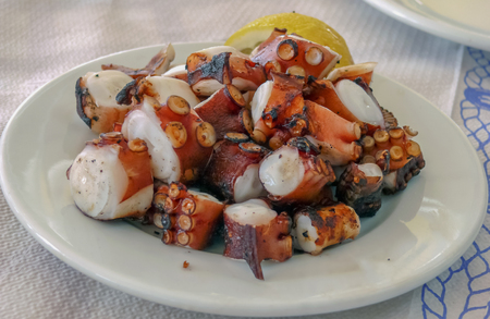 taverna: Grilled octopus in pieces on the white plate. Greek taverna