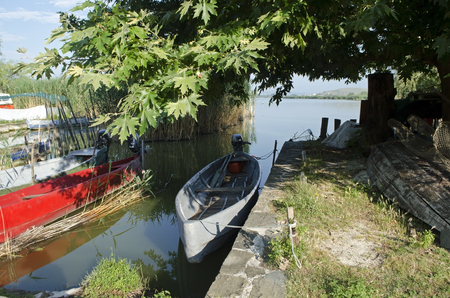 Morning backwater in the summer with boats waiting at the bank