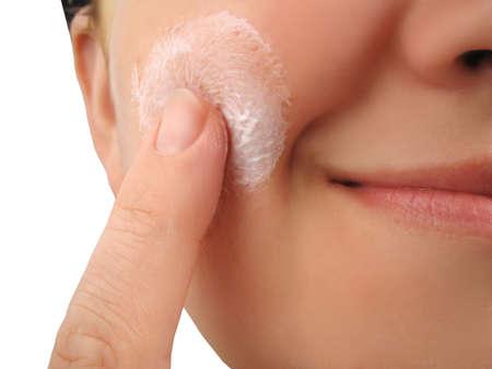 regime: woman applies moisturizer onto face Stock Photo