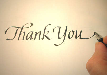 person writing thank you in calligraphy