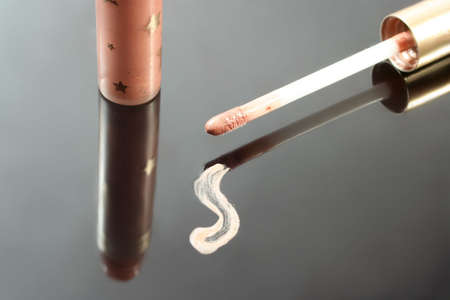 smeared: smudge of beige lip gloss, applicator, and tube