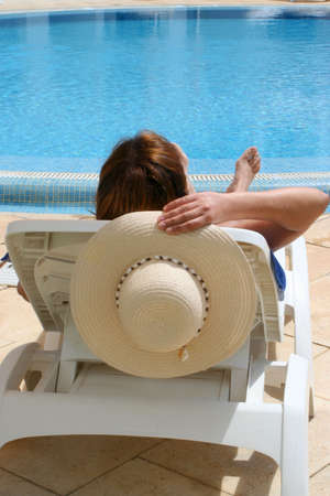 poolside: woman relaxes by the pool