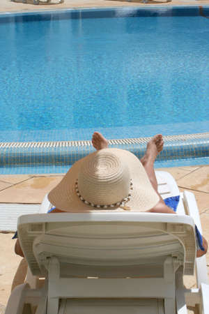 relaxes: woman relaxes by the pool