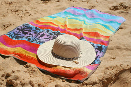 oceanic: beach hat and towel in the sand