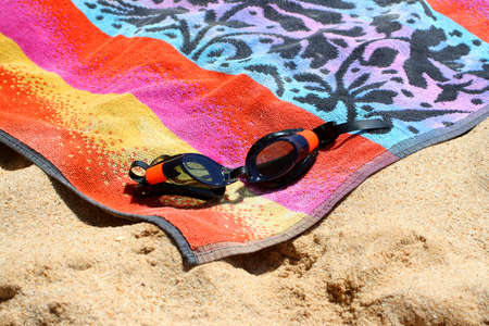 sandy beach with goggles and towel