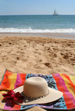 beach hat and flower on towel  in the sand with sailboat in the background