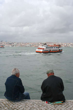 goes: fisherman sit on wharf as ferry goes by with Lisbon in the horizon