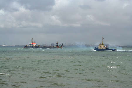 tugboat polluting the air and freighter in background Reklamní fotografie