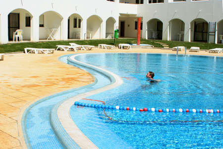 boy wades in the pool at resort Stock Photo