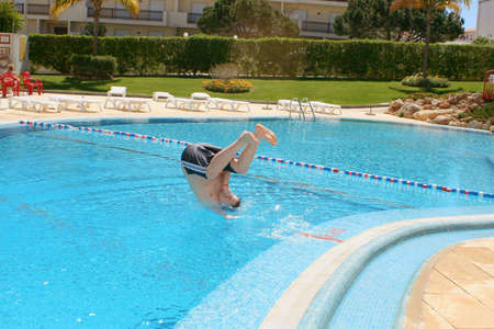 boy dives into a pool at resort