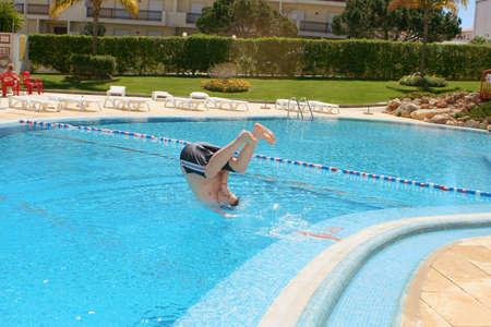 piscina olimpica: el muchacho se zambulle en una piscina en el recurso Editorial