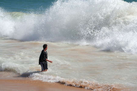 wetness: boy stands at shore with dangerous wave approaching