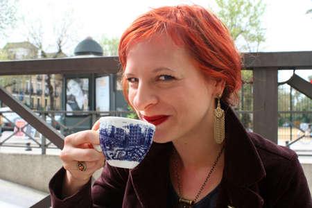 sorbo: La mujer goza del caf� en un caf� del aire libre en Sevilla, Espa�a