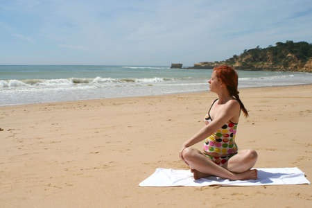woman does yoga and meditation on beach Imagens