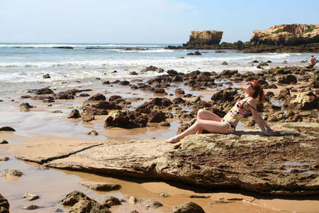 woman soaks up the sun at the beach in the Algarve, Portugal