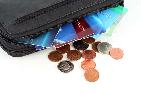 wallet with credit cards and change scattered about