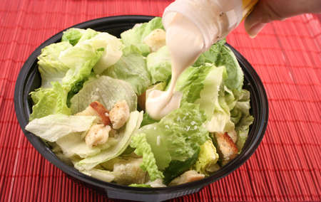 caesar salad: pouring dressing over lettuce for a caesar salad