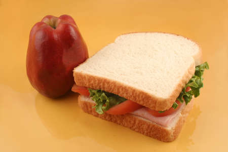 ham sandwich with tomatoes and lettuce and an apple