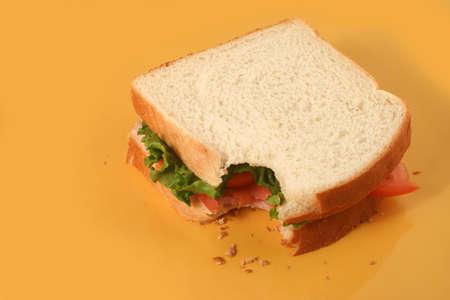 ham sandwich: Mangiare un panino con il prosciutto di lattuga e pomodori