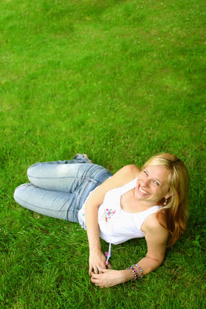 relaxes: smiling woman relaxes on the grass Stock Photo