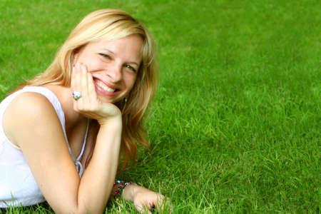 smiling woman relaxes on the grass Stock Photo