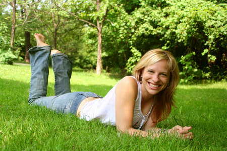 relaxes: smiling woman lays and relaxes on the grass