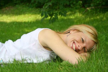 relaxes: la mujer sonriente relaja en la hierba Foto de archivo