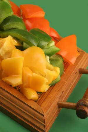 cut up green, yellow and orange peppers photo