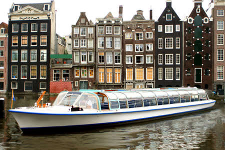 gabled: Amsterdam canal with with sightseeing tourism boat